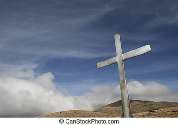 Steel cross against a blue sky with dramatic clouds