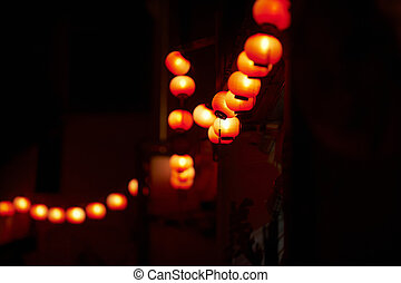 String of orange and red chinese lanterns at night hung up...