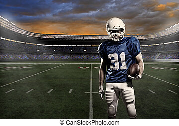 Football player with a blue uniform, in a stadium with fans...