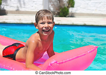 Smiling boy lies on pink mattress in the pool