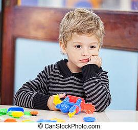 Menino, com, blocos, olhar, afastado, em, pré-escolar