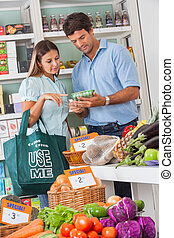 Couple Reading Product Details In Supermarket - Mid adult...
