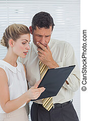 Business people looking at clipboard