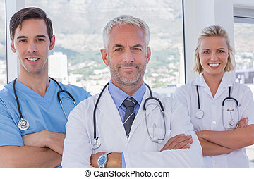 Group of doctor and nurses standing together with arms...