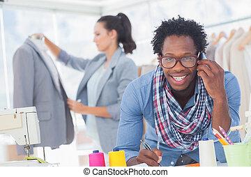 Smiling fashion designer on the phone