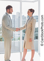 Business people shaking hands and smiling in a large office