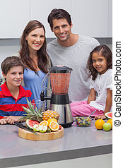 Smiling family using a blender together