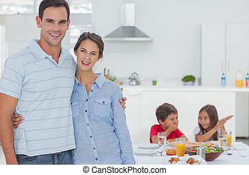 Couple standing in front of children at the table for the...