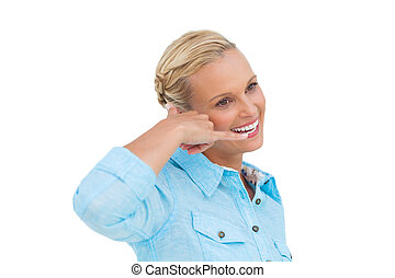 Attractive blonde doing a symbol of phone with her hand and...