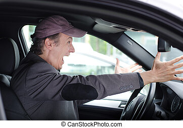 Angry upset man at wheel driving his car screaming - Angry...