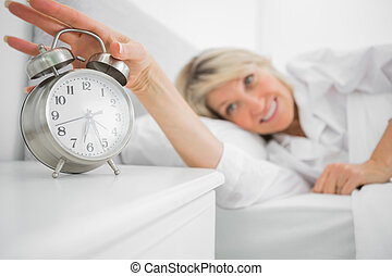 Blonde woman turning off alarm clock at home in bedroom