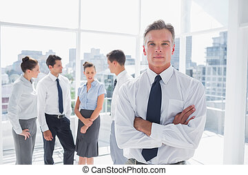 Serious boss with arms folded standing in a modern office...