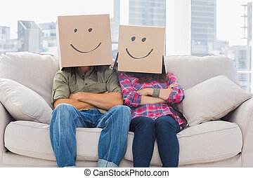 Funny workers with arms crossed wearing boxes on their heads...