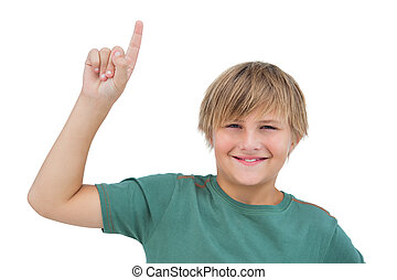 Little boy pointing upwards on white background