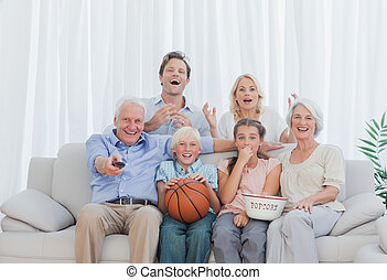 Extended family watching the television on couch