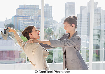 Businesswomen having a massive fight in a bright office