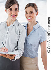 Young businesswomen smiling at camera in their office