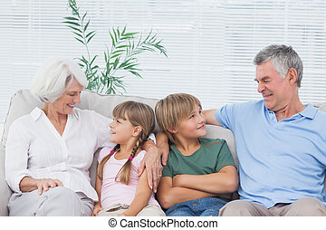 Grandparents speaking with their grandchildren in the living...
