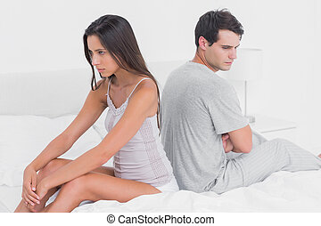 Sad couple ignoring each other sitting back to back on bed...
