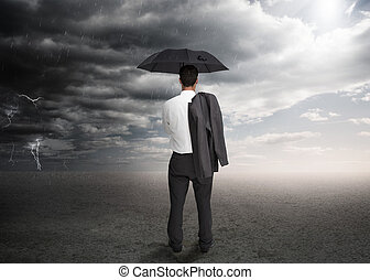 Businessman holding an umbrella and a jacket over his...