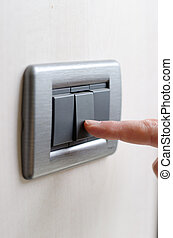 Finger pressing light switch, turning it on or off - Closeup...