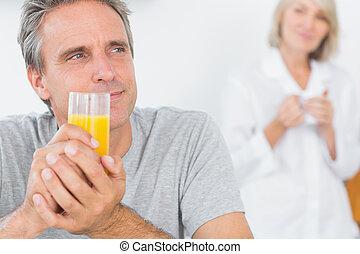 Smiling man drinking orange juice in kitchen with partner...