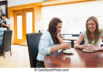 Two woman sitting in cafeteria and drinking coffee while...
