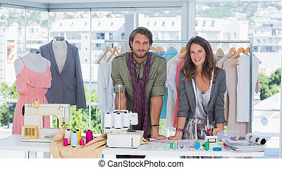 Fashion designers leaning on desk with spools of thread and...