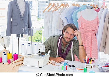 Thoughtful fashion designer sitting behind his desk