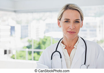 Smiling blonde doctor holding a clipboard