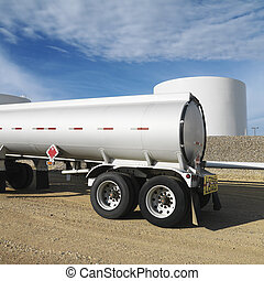 Fuel tanker and fuel farm. - Side view of fuel tanker truck...