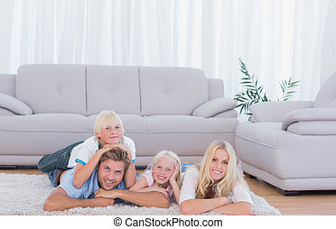 Family lying on the carpet and smiling at camera