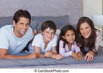 Cheerful family lying on bed at home