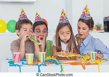 Little girl blowing her candles during her birthday party...