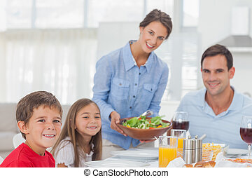 Portrait of a woman bringing a salad to her family