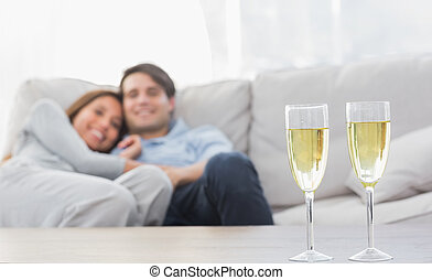 Couple resting on a couch with flutes of champagne on a...