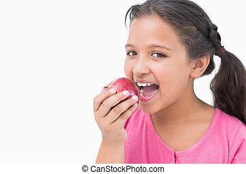 Little girl eating apple on white background
