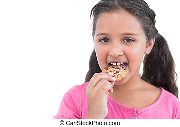 Happy little girl eating a cookie