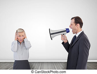 Businessman shouting with a megaphone at his colleague -...