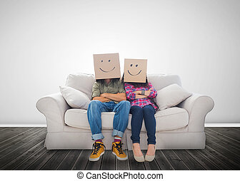 Funny couple wearing boxes on their head on a couch