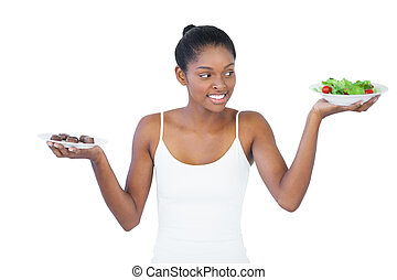 Cheerful woman deciding to eat healthily or not on white...