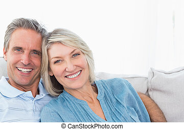 Cheerful couple relaxing on their couch smiling at camera