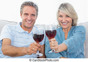 Couple toasting to the camera with red wine on the sofa at...