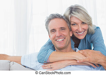 Couple smiling at the camera at home in living room