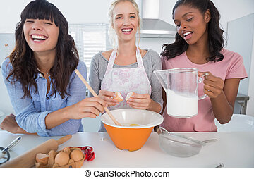 Laughing friends making pastry together at home in kitchen