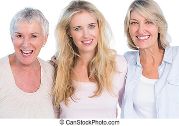 Three generations of cheerful women smiling at camera on...