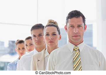 Serious handsome businessman standing with team in their...