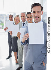 Business team in a line holding white pages smiling at...