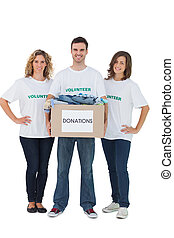 Group of volunteers holding donation box with clothes on...