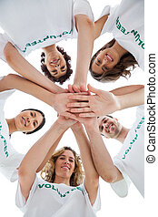 Smiling group of volunteers piling up their hands on white...